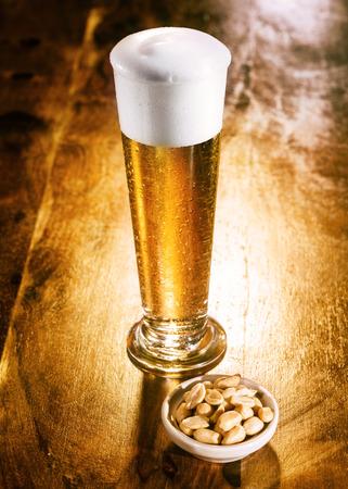 frothy: Elegante bicchiere alto di birra con una buona testa schiumoso servito con una piccola ciotola di dadi come snack su un contatore di legno in un ristorante o bar