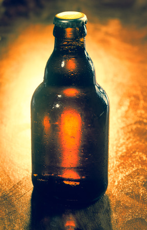 unlabeled: Unopened unlabeled brown glass bottle of beer backlit on a wooden surface with corner vignetting for your advertising or marketing