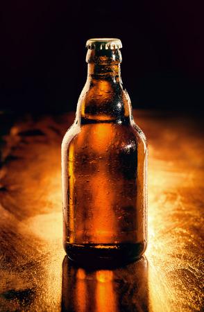 botellas de cerveza: Sin abrir la botella de vidrio marrón de retroiluminada cerveza helada en una barra de bar de madera, sin etiqueta para su publicidad Foto de archivo