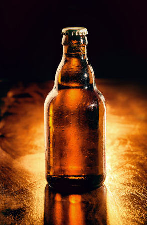 unopened: Unopened brown glass bottle of chilled beer backlit on a wooden bar counter , unlabeled for your advertising