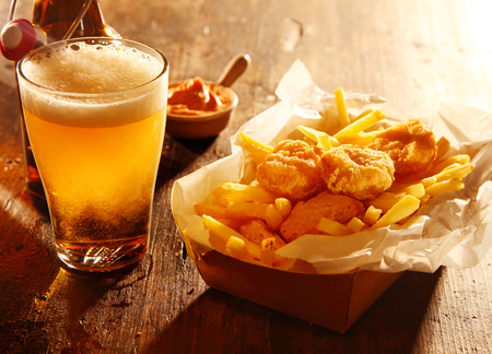 snacks: Chilled glass of draft beer served with fried battered fish and French fries accompanied by a savory dip in a bar, tavern or pub
