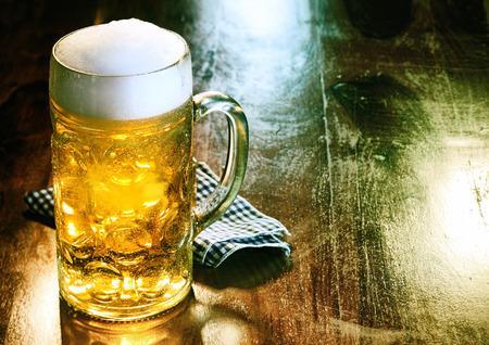 골든 에일 또는 초안과 유리 맥주 머그잔을 얹어 거품 머리 서 또는 바에서 술집에서 오래 된 나무 카운터 copyspace와 술집
