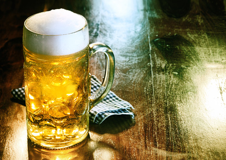 Glass beer mug with golden ale or draft topped with a frothy head standing on an old wood counter in a bar or pub with copyspace
