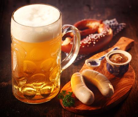 ガラスの大型ジョッキまたはドイツのソーセージとコールド ドラフト ビールとマスタードのプレッツェルのマグカップで提供しています軽食の木製