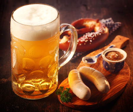 Glass tankard or mug of cold draft beer with German sausages and pretzels with mustard served on a wooden board for refreshments conceptual of Oktoberfest Foto de archivo