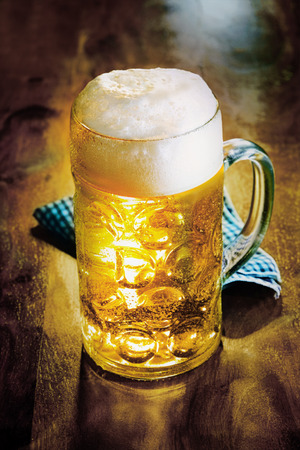 Glass tankard of cold golden ale or beer with a good frothy head served on a wooden counter with a napkin, close up view photo