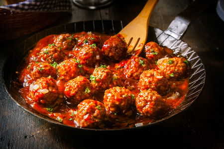 mincing: Delicious meatballs made from ground beef in a spicy tomato sauce served in a skillet or old metal pan in a restaurant