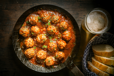 rustic food: Rustic wholesome lunch of tasty savory meatballs in a spicy tomato and herb sauce served with a glass of beer and sliced baguette, close up overhead view