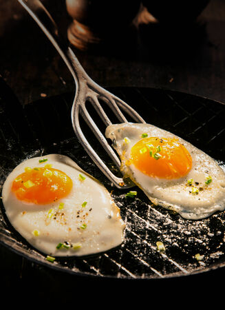 cholesterol free: Two delicious free range fried eggs with dark yellow yolks seaoned with salt and aromatic herbs for a healthy breakfast and start to the day Stock Photo