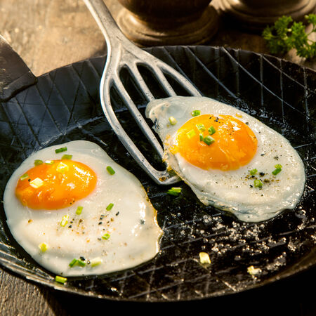 cholesterol free: Two fried eggs seasoned with herbs and salt in an old metal pan or griddle ready to be served for a delicious breakfast