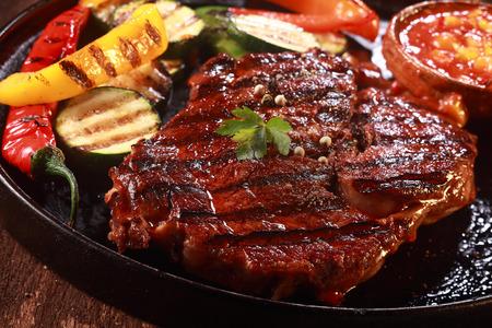 Close-up van gegrilde biefstuk is op gietijzeren pan met gegrilde groenten op de zijkant