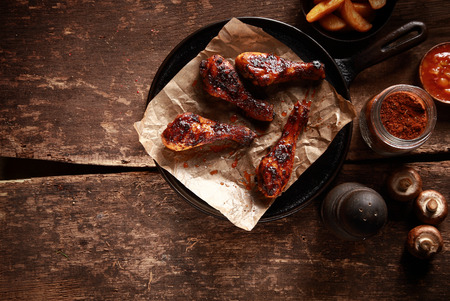 High Angle Looking Down at Saucy Barbecued Chicken Drumsticks on Cast Iron Pan Accompanied by Spices and Ingredients