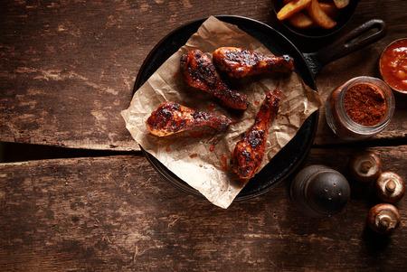 alitas de pollo: Elevada Mirar hacia abajo en Saucy Barbecued Palillos de pollo en la cacerola de hierro fundido Acompa�ado de especias e ingredientes