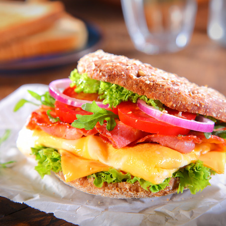 mouth watering: Close up Mouth Watering Burger with Bacon, Cheese, Tomatoes, Onions and Lettuce on Top of Burger Paper. Stock Photo