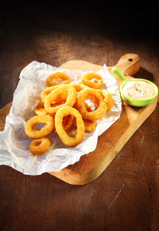 mouth watering: Cooked Mouth Watering Squid Rings with Sour Cream Sauce on White Paper Above Wooden Serving Board.