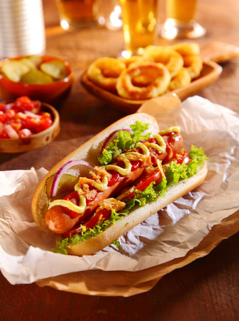 hot dog: Traditional hot dog with a smoked frankfurter on a fresh roll garnished with mustard and ketchup and served with lettuce, tomato and onion