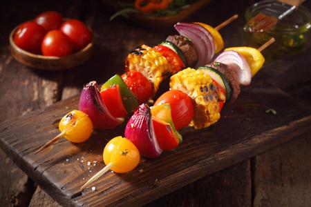 Kleurrijke veganistisch of vegetarisch groente spiesjes met vers geroosterde of gegrilde paprika, ui, champignons, maïs, aubergine en cherry tomaten, close-up uitzicht op een houten plank