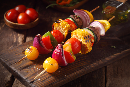 Colorful vegan or vegetarian vegetable skewers with fresh roasted or grilled sweet peppers, onion, mushroom, corn, eggplant and cherry tomatoes, close up view on a wooden board Archivio Fotografico