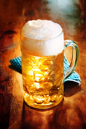 distinctive: Glass tankard of golden frothy craft beer brewed and distributed locally for its distinctive flavor on a wooden counter in a pub or bar