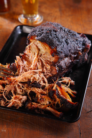 Close Up Mouth Watering Pulled Pork on Black Tray Above Wooden Table. Archivio Fotografico