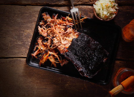 Aerial Shot of Mouth Watering Pulled Pork Dish on Black Serving Tray with Fork. Served on Wooden Table.