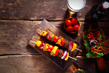 Delicious bar lunch of fresh vegan or vegetarian kebabs with assorted roasted colorful vegetables on skewers served on a rustic wood table with a beer and salad, with copyspace photo