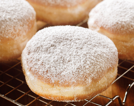 powdered sugar: Delicious freshly baked cream donut sprinkled with powdered sugar cooling on a wire rack in the kitchen