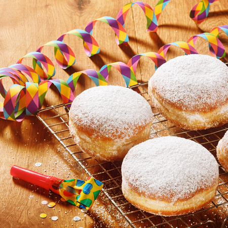 Close up Delicious Powdered Sugar Raised Donuts on Screen with Carnival Props on Top of Wooden Table photo