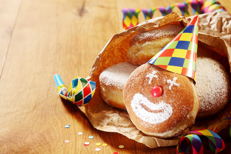 clown birthday: Close up Gourmet Carnival Powdered Sugar Raised Donuts on Paper, Placed on Wooden Table.