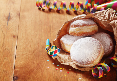 Close up Carnival Donuts with Powdered Sugar on Paper with Colored Props on Sides, Placed on Wooden Table. Stock Photo