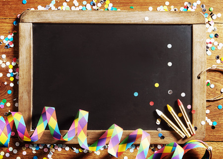 Close up Carnival Black Board, Decorated with Confetti, with Copy Space on Wooden Background. Stockfoto