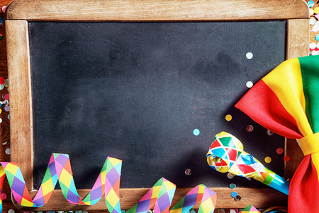 Close up Colorful Carnival Paper Streamers, Whistle and Ribbon in Front Empty Black Board. Emphasizing Copy Space.