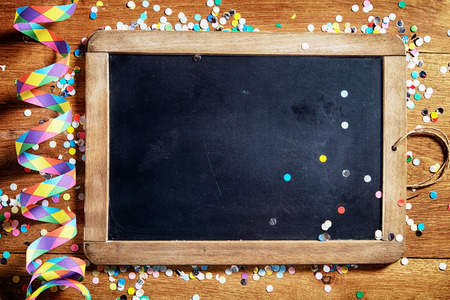 Close up Empty Black Board on Wooden Table with Colorful Streamers and Confetti. Emphasizing Copy Space.