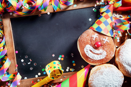 emphasizing: Close up Empty Black Board with Decorated Carnival Donuts and Festival Props. Emphasizing Copy Space at the Center for Texts. Stock Photo