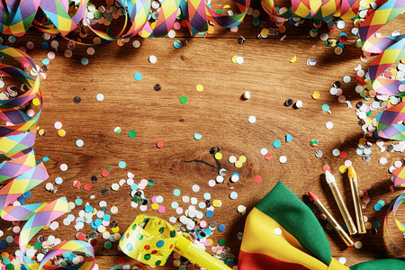 carnival border: Close up Wooden Table with Festival Props - Confetti, Paper Streamers, Whistle, Ribbon and Pencil. Emphasizing Copy Space.