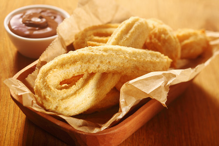 piped: Close up Tasty Churros Snacks on Tray, with Paper, Placed on Wooden Table with Chocolate Dipping Sauce.