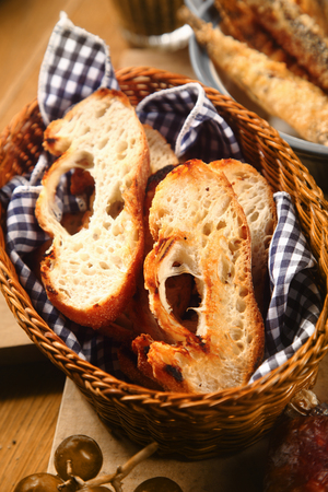 accompaniment: View from above of slices of fresh and toasted baguette with a texture full of holes in a bread basket with a blue and white checked napkin Stock Photo