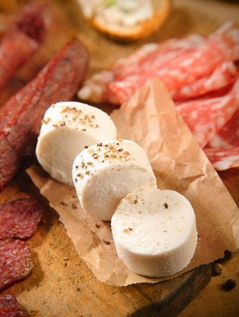 goat cheese: Rounds of fresh goat milk cheese on brown paper surrounded by sliced spicy Italian salami