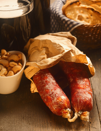 be prepared: Two whole spicy Italian salami sausages in a brown paper packet with a bowl of cashew nuts waiting to be prepared for appetizers or tapas Stock Photo