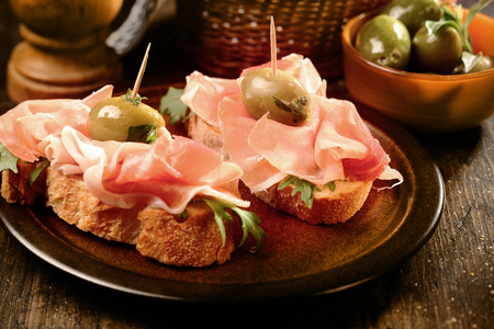 cured ham: Canapes or tapas with proscuitto ham and olives on crusty fresh baguette served as appetizers or snacks at a party