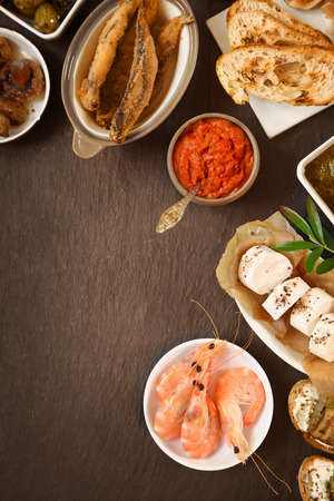 Freshly Made Various Tapas on Brown Wooden Table with Copy Space for Texts. photo