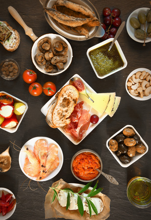 食品のコンセプト - 茶色の木製のテーブルの上にさまざまな食欲をそそるタパス 写真素材