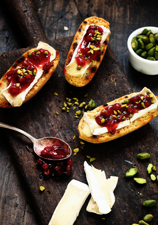 Tasty camembert and cranberry coulis sprinkled with chopped fresh pistachio nuts on toasted rolls being prepared in the kitchen, with copyspace photo