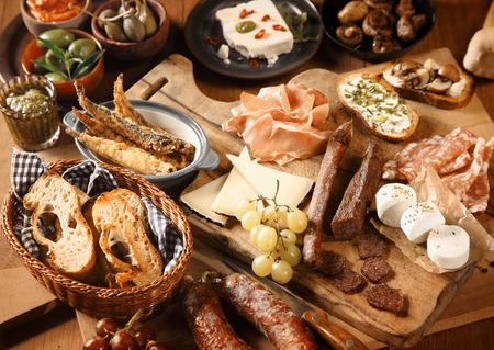emphasising: Close up Appena fatto appetitosi Vari Tapas sul tavolo in legno, sottolineando pane, formaggio, uva e carni. Archivio Fotografico