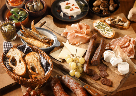 grapes and mushrooms: Close up Freshly Made Appetizing Various Tapas on Wooden Table, Emphasizing Bread, Cheese, Grapes and Meats. Stock Photo