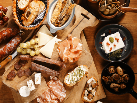 emphasizing: Close up High Angle Shot of Assorted Mouth Watering Tapas on Wooden Table, Emphasizing Meats, Cheese and Breads Stock Photo