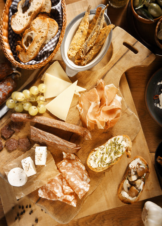 emphasizing: Close up Assorted Appetizing Tapas on Wooden Board, Emphasizing Ham, Cheese and Bread.