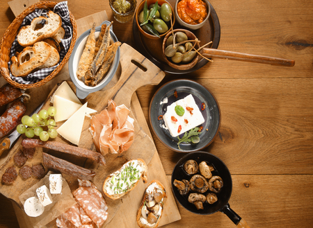 buffet: High Angle Shot of Various Freshly Made Mouth Watering Appetizers and Snacks on Wooden Board and Plates on Top of Wooden Table