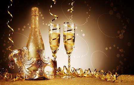近くには黄金祭ボトルと仮面舞踏会マスクとワインのガラス、のぼり、キラキラのテーブルの前に抽象的なグラデーションのブラウンの背景上で装