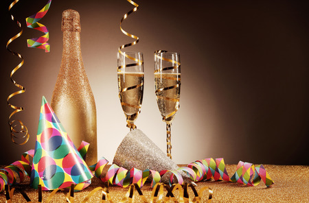 merrymaking: Close up Party Hats, Golden Wines and Paper Streamers on Glittery Table in front Gradient Brown Background. Emphasizing Copy Space. Stock Photo